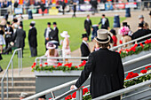 Seen from behind in the foreground, a man in black tails and a grey top hat is standing on the steps, looking over at the people in tails and summer dresses on one of the lawns in the Royal Enclosure at Royal Ascot, Ascot, England