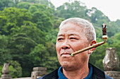 A man smoking in Leshan Giant Buddha scenic area, Sichuan Province, China