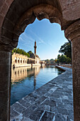 Chamber of Abraham and a minaret reflected in the tranquil water of a lake, Sanliurfa, Turkey