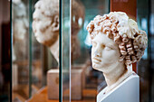 Sculpture of female head with curly hair at an archaeological museum, Corinth, Greece