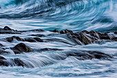 Long exposure of waves striking the coastline and flowing over rocks, Iceland