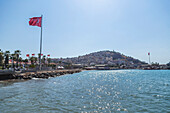 The Turkish flag flies in a blue sky on a sunny day next to the Mediterranean sea, Kusadasi, Izmir, Turkey