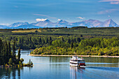 Paddlewheel boat on lake with tree lined shoreline, hills and mountains in the background and blue sky and clouds, Calgary, Alberta, Canada