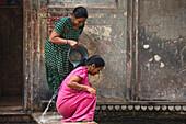 Two women having a ritual bath in Galtaji temple, Jaipur, Rajasthan, India