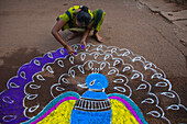 A young Indian female painting a peacock on the street in celebration of a festival, Betul Beach, Goa, India