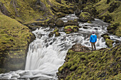 Tourist at a waterfall on the hiking trail above Skogafoss Waterfall, Skogar, South Region Sudurland, Iceland, Polar Regions