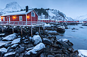 Typical fishermen houses called rorbu in the snowy landscape at dusk, Nusfjord, Nordland County, Lofoten Islands, Norway, Scandinavia, Europe