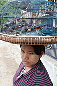 Woman with thanaka on her cheeks and trapped birds in a basket on her head, asking for people to pay to set them free, Mandalay, Myanmar Burma, Asia