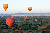 Hot air balloons flying over the terracotta temples of Bagan with the Irrawaddy river in the distance, Bagan Pagan, Mandalay Division, Myanmar Burma, Asia