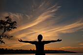 Silhouette young woman standing with arms outstretched on lakeshore during sunset