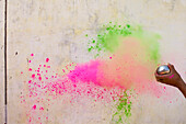 Cropped image of hand throwing powder paints on wall during Holi