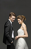 Side view of newly wed couple over gray background