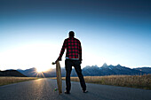 A skateboarder pauses to watch the sun set over the Grand Teton Mountains in Jackson Hole, Wyoming.