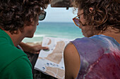 Couple of young person (25-35 years old) inside of their car looking at a map with the ocean in the background.