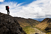 A backpacker looks over the valley at the base of El Altar, Ecuador's 5th tallest volcano.