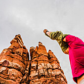 Low angle view of woman with her hands overhead, taking off her shirt among unusual sandstone formations in the Canyonlands National Park.