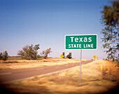A Texas State Line sign on a back road in Oklahoma lets the driver know that they are about to enter the Great State.