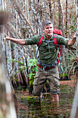 50+ male hiker treks through knee deep water in a cypress grove in the Florida Everglades in Winter.  He is wearing a red backpack and green and tan hiking apparel.