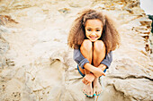Mixed race girl hugging knees on rock