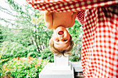 Baby boy hanging upside down outdoors
