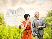 Caucasian couple enjoying wine in vineyard