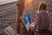 Caucasian girl painting on remote lake