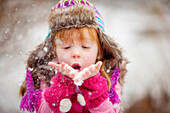 Caucasian girl blowing handful of snow