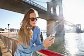 Caucasian woman using cell phone on waterfront, New York, New York, United States