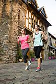 Caucasian friends jogging in village
