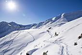 Gruppe Schneeschuhwanderer im Schwarzwassertal bei Sonnenschein und Schnee, Vorarlberg, Österreich