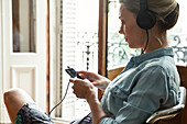 Woman listening to music playing on smartphone