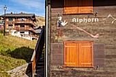 dessin d'un homme jouant du cor des alpes sur la facade d'un chalet en bois typique dans le centre du village de bettmeralp, station de ski, bettmeralp, canton du valais, suisse