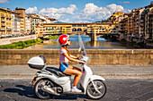 jeune femme filant sur sa vespa avec en fond le ponte vecchio le pont emblematique de florence, florence, toscane, italie, union europeenne