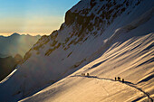 mountaineers roped together to climb to the barre des ecrins at sunrise, massif des ecrins, vallouise, hautes-alpes (05), provence-alpes-cote d'azur, paca, france