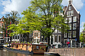 characteristic scene around the princengracht canal (houseboats and typical buildings), amsterdam, holland