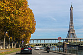 the eiffel tower and a street along the riverbanks lined with trees in autumn colors, paris (75), france