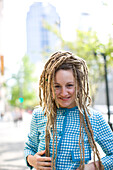 Eliza Carlson smiles at the camera while dressed in a women's business suit from the 1960's. Carlson is sporting a dreadlock hairstyle and is standing in the downtown area of Seattle, Washington.