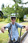 Adam Welch poses for a portrait of his cruiser bike. Welch is wearing a top hat, mirrored sunglasses, and a smile on his face. Sandpoint, Idaho.