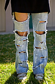 Waist down image of a woman in cut up jeans.