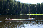 Two teenage boys create the illusion of one long person while lying down in an aluminum canoe in the middle of a small Lake in western Montana. The two boys are cousins and get together at their summer home just outside of Butte