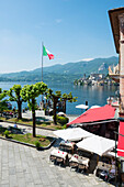 Flag of Italy flying at the waterfront beside a restaurant patio on Lake Orta Orta, Piedmont, Italy