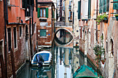 Boats moored in a tranquil canal between buildings Venice, Italy