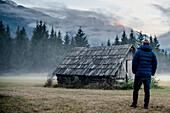 Mann steht vor einer Hütte zwischen Ehrwald und Biberwier, Mieminger Kette, Zugspitze, Alpen, Nebel, Tirol, Österreich