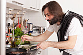 Mid adult man preparing meat in domestic kitchen
