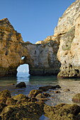 Weathered sandstone cliffs and sea stacks at Ponta da Piedade in morning light with a yacht framed by a rock arch, Lagos, Algarve, Portugal, Europe