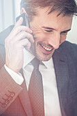 Businessman talking on cell phone, smiling