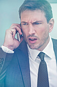 Businessman receiving bad news by cell phone