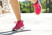 Woman jogging in sports shoes, cropped