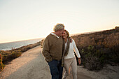 Older Caucasian couple walking on dirt path