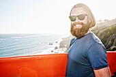 Caucasian man holding surfboard on coastal cliff